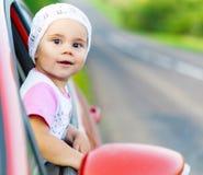 画象愉快儿童女孩黏附他们朝向汽车胜利 库存照片