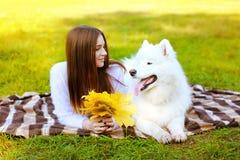 画象愉快的俏丽的妇女和白色萨莫耶特人尾随获得乐趣 免版税库存照片