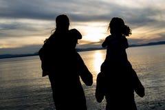 画象愉快的美丽的家庭四一起在日落 免版税库存图片