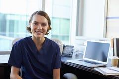 画象护士佩带洗刷坐在书桌在办公室 免版税库存照片