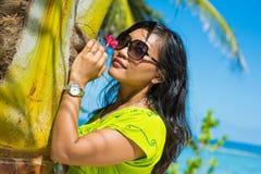 画象接近年轻美丽的亚裔女孩在热带海滩的plam树附近 免版税库存图片