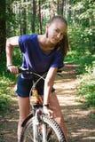 画象有一辆自行车的美丽的少妇在公园背景 库存照片