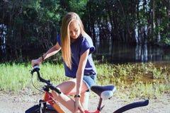 画象有一辆自行车的美丽的少妇在公园背景 免版税库存图片