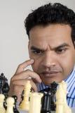 象棋移动球员正确的认为的年轻人 图库摄影