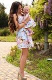 象母亲喜欢女儿 在相似的礼服的美丽的家庭 免版税库存照片