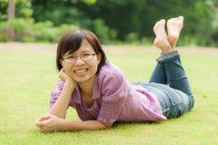 画象浪漫,有说谎在绿草的短发的妇女 图库摄影
