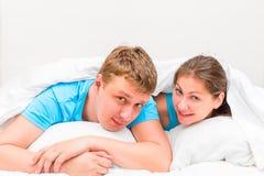 画象男人和妇女在毯子下的30岁 免版税库存图片