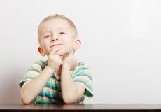 画象白肤金发的沉思周道的男孩儿童孩子在室内桌上 免版税库存图片