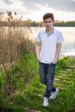 画象的青少年的男孩关闭在夏天湖自然背景 免版税库存图片