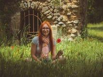 画象相当,年轻人,玻璃的逗人喜爱的妇女坐有鸦片花的,庞贝城,意大利绿色草甸 免版税库存照片