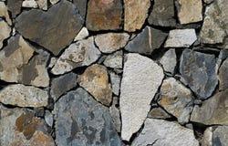 象石墙的马赛克用不同的色的石头 免版税库存图片