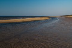 象织地不很细沙子-波罗的海与白色沙子的海湾海滩的点心在日落 库存图片