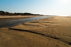 象织地不很细沙子-波罗的海与白色沙子的海湾海滩的点心在日落 图库摄影