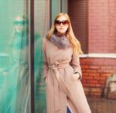 画象美丽的典雅的白肤金发的妇女佩带的外套夹克和太阳镜在城市 免版税库存图片