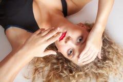 画象美丽的白肤金发的女孩在地板演播室射击做说谎 免版税库存照片