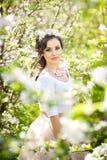 画象美好女孩摆在室外与樱桃树的花在开花的在一个明亮的春日期间 库存图片