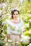 画象美好女孩摆在室外与樱桃树的花在开花的在一个明亮的春日期间 库存照片