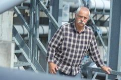 画象老人支持的金属楼梯 库存照片