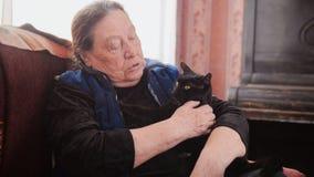画象老妇人在家-资深妇女坐有恶意嘘声的沙发-接近  库存图片