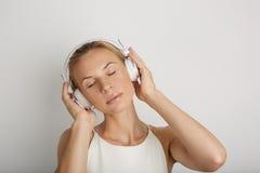 画象英俊的少妇听的耳机 作音乐播放器空白黄色颜色背景 俏丽的女孩享用 库存照片