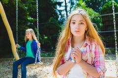 画象英俊青少年恳求或beging在公园 在背景乘坐摇摆的其他女孩 图库摄影