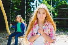 画象英俊青少年恳求或beging在公园 在背景乘坐摇摆的其他女孩 免版税库存图片