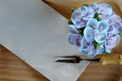 象蓝色八仙花属花的蓝色杯形蛋糕设计奶油在有包装纸餐巾和一点叉子的木盘子服务 库存照片