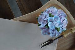 象蓝色八仙花属花的蓝色杯形蛋糕设计奶油在有包装纸餐巾和一点叉子的木盘子服务 免版税图库摄影