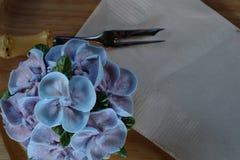 象蓝色八仙花属花的蓝色杯形蛋糕设计奶油在有包装纸餐巾和一点叉子的木盘子服务 免版税库存照片