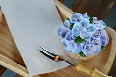 象蓝色八仙花属花的蓝色杯形蛋糕设计奶油在有包装纸餐巾和一点叉子的木盘子服务 图库摄影