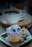 象蓝色八仙花属花的蓝色杯形蛋糕设计奶油服务用在木桌背景的热的无奶咖啡 库存照片