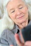 画象资深妇女键入的sms 免版税库存照片