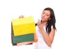 画象逗人喜爱的少妇移动电话,当拿着购物的ba时 库存照片