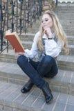画象逗人喜爱认为和有走下去坐台阶的书的平静的白种人白肤金发的女性户外和读 免版税图库摄影