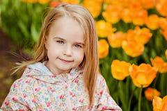 画象非常逗人喜爱的俏丽的女孩白肤金发在一桃红色斗篷arou 库存图片
