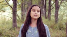画象 一个小害羞的女孩在公园走并且微笑 股票录像