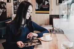 画象年轻华美的女孩饮用的茶和周道看在咖啡店窗口外面,当享用她时 库存照片