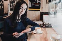 画象年轻华美的女孩饮用的茶和周道看在咖啡店窗口外面,当享用她时 免版税库存照片