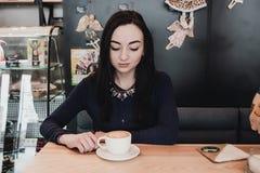 画象年轻华美的女孩饮用的茶和周道看在咖啡店窗口外面,当享用她时 免版税库存图片