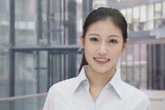 画象年轻确信的微笑的女实业家,修造外部在背景 免版税图库摄影