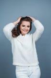 画象年轻美丽的女孩微笑和佩带被编织的白色毛线衣,隔绝在灰色背景 免版税库存照片