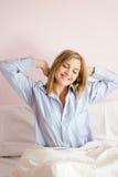 画象年轻美好白肤金发女商人愉快微笑的舒展在床松弛眼睛关闭了 免版税库存图片
