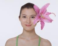 画象年轻,微笑,有在她的耳朵后被卷起的一朵大桃红色花的美丽的妇女,演播室射击 库存图片