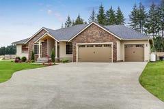 豪华一平实房子外部与砖修剪和车库 库存图片