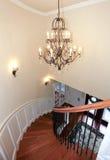 豪华与枝形吊灯和harwood的弯曲的楼梯。 免版税库存图片