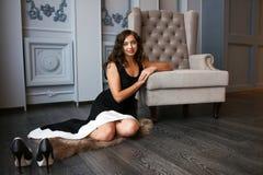 豪华内部开会的美丽的妇女在扶手椅子旁边的地板上 图库摄影