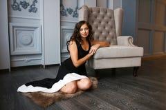 豪华内部开会的美丽的妇女在扶手椅子旁边的地板上 免版税库存照片