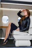 豪华内部的年轻美丽的妇女在企业喷气机 免版税库存图片
