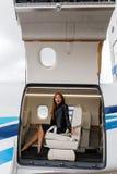 豪华内部的年轻美丽的妇女在企业喷气机 免版税库存照片
