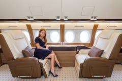 豪华内部的年轻美丽的妇女在企业喷气机 库存图片